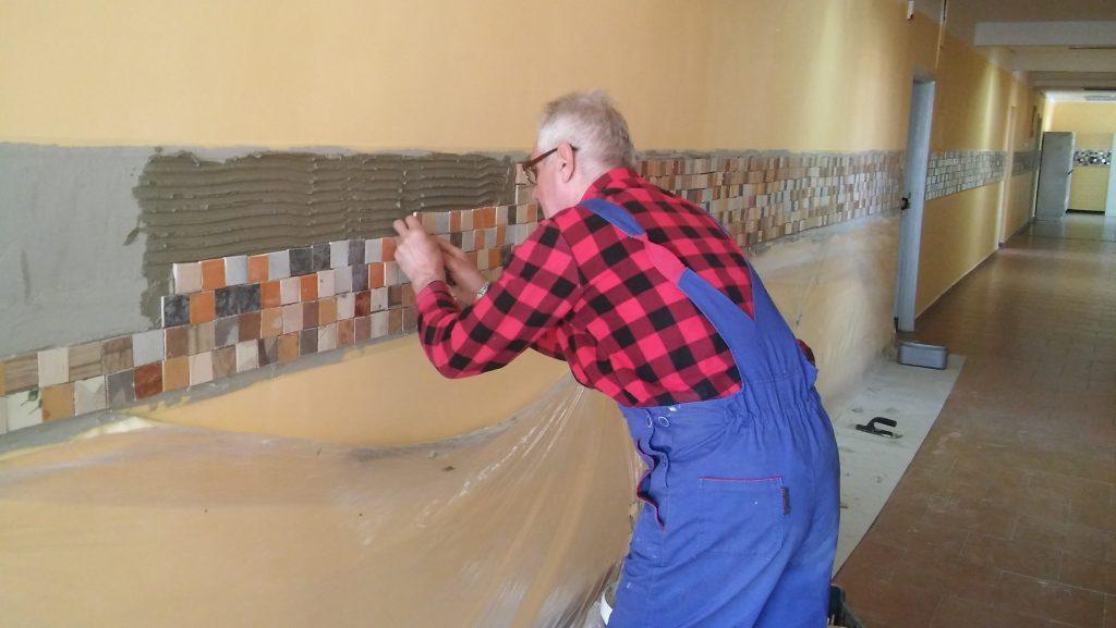 Centrum Integracji Społecznej i pomoc socjalna - na zdjęciu starszy mężczyzna wykonujący prace remontowe, układa mozaikę na ścianie