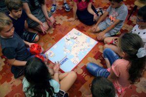 Wolontariusze IB Polska z projektów Wolontariatu Europejskiego grają z dziećmi w grę edukacyjną o przedsiębiorczości, którą sami stworzyli