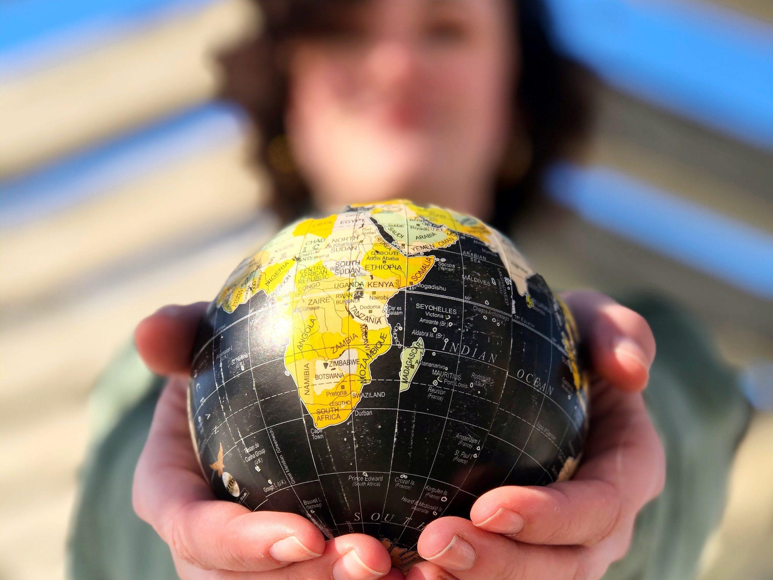 Punkt Informacji dla Obcokrajowców w Krakowie - rozszerzenie oferty językowej udzielanych (zdjęcie kobiety trzymającej mały globus) porad