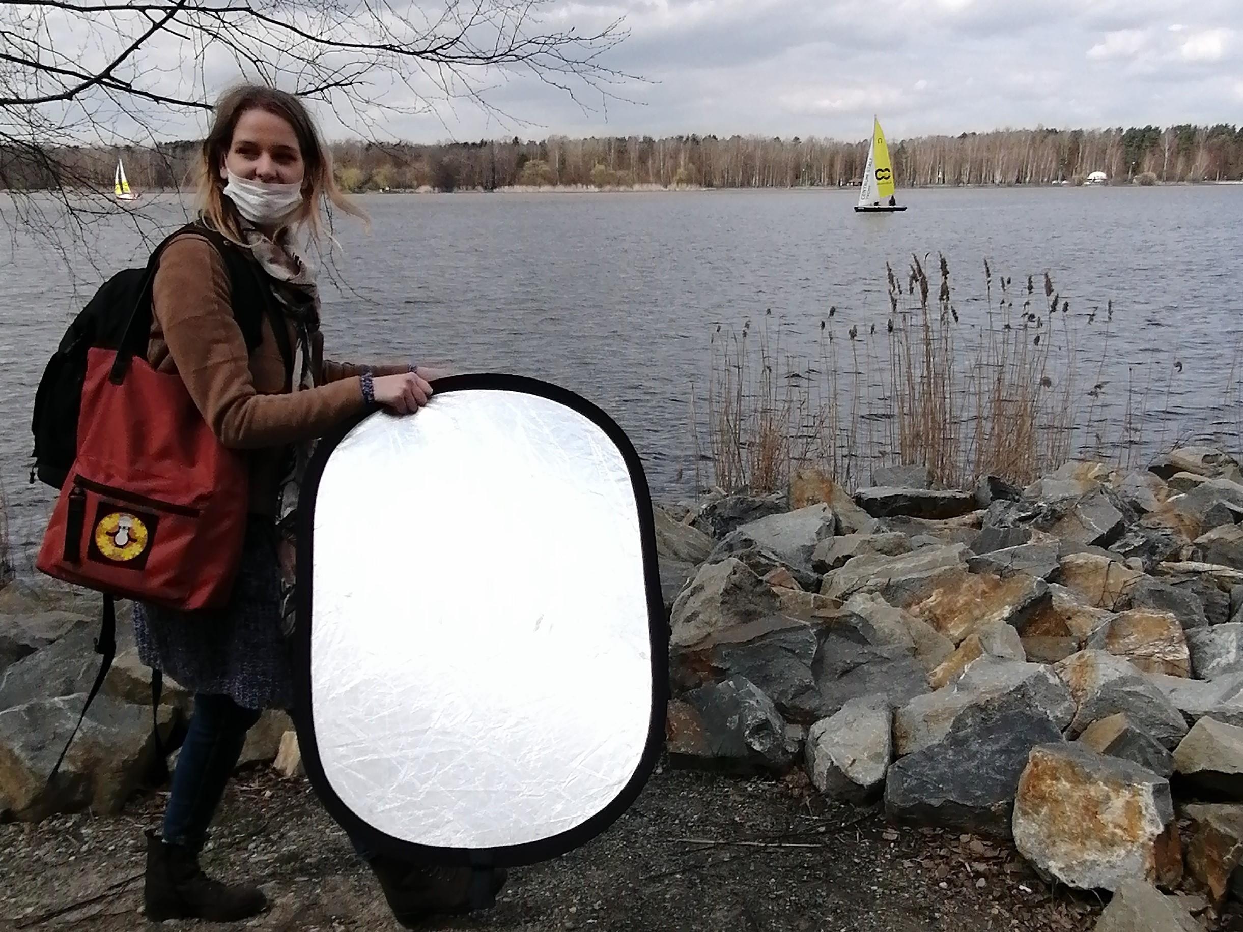Plenerowe warsztaty fotograficzne Klub Seniora Platyna- instruktorka z blendą fotograficzną, w tle Jezioro Paprocany i żaglówka
