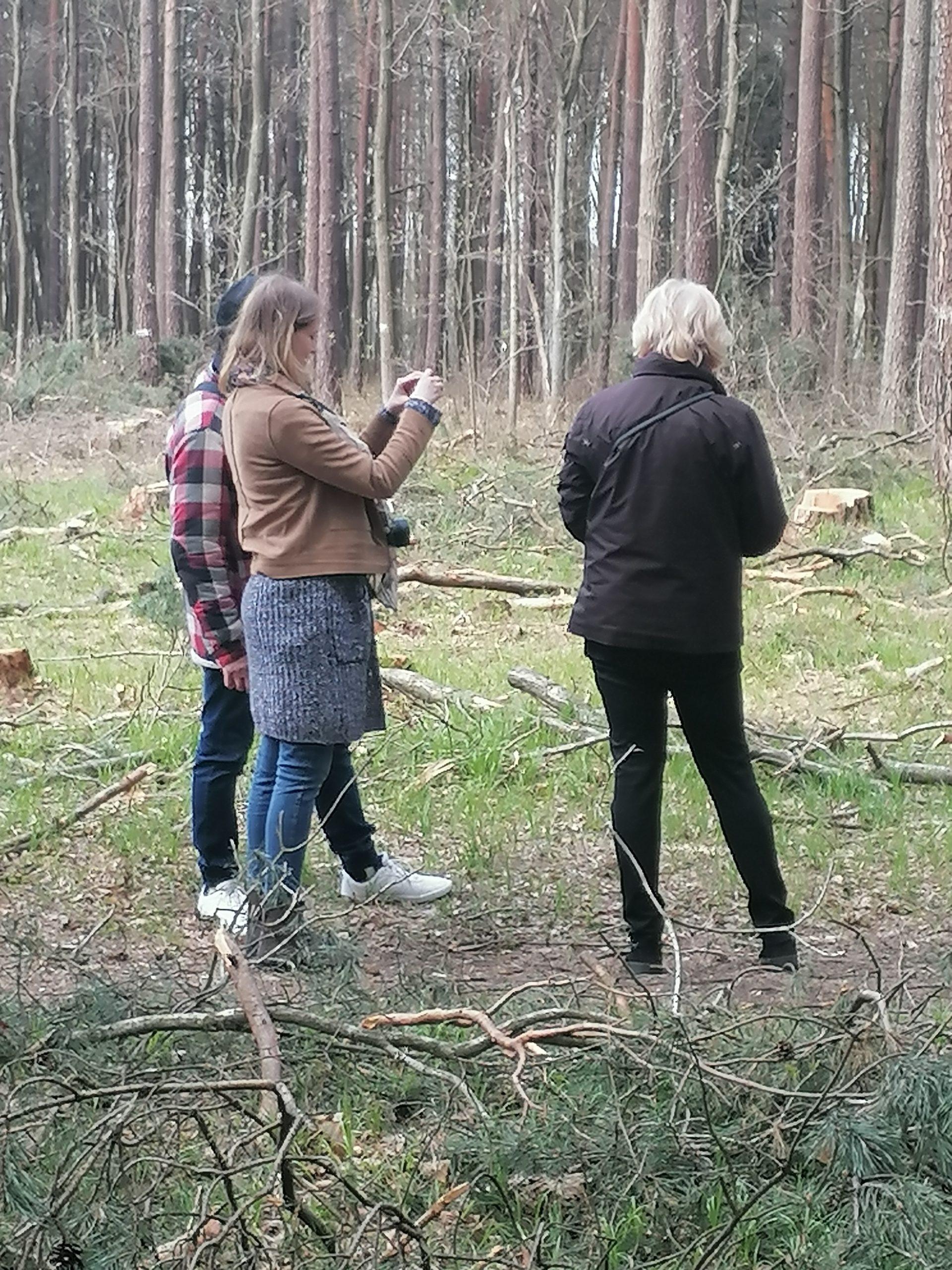 Plenerowe warsztaty fotograficzne Klub Seniora Platyna - zdjęcie pokazuje las i uczestników fotografujących na leśnej polanie. Nad procesem czuwa instruktorka.
