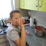Asystent osobisty osoby z niepełnosprawnościami - podopieczny Mikołaj pije koktajl truskawkowy