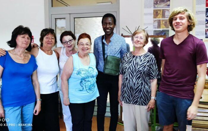 Spotkanie seniorów z praktykantem Centrum Wielokulturowego, który pochodzi z Ruandy. Tłumaczy wolontariusz Ignacy.